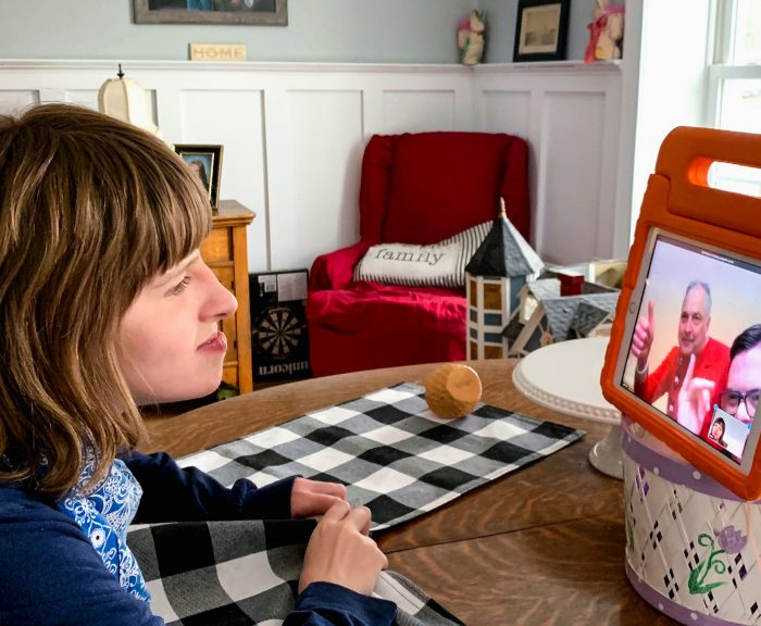 Maia Chamberlain at a table in front of an ipad
