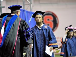 student crosses the stage in cap and gown